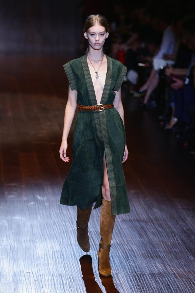 Gucci, MFW, collezione Primavera-Estate 2015: l'abito è in camoscio verde muschio aperto completamente sul davanti e strizzato in vita da una cintura in cuoio. Gli stivali in camoscio arrivano sotto il ginocchio