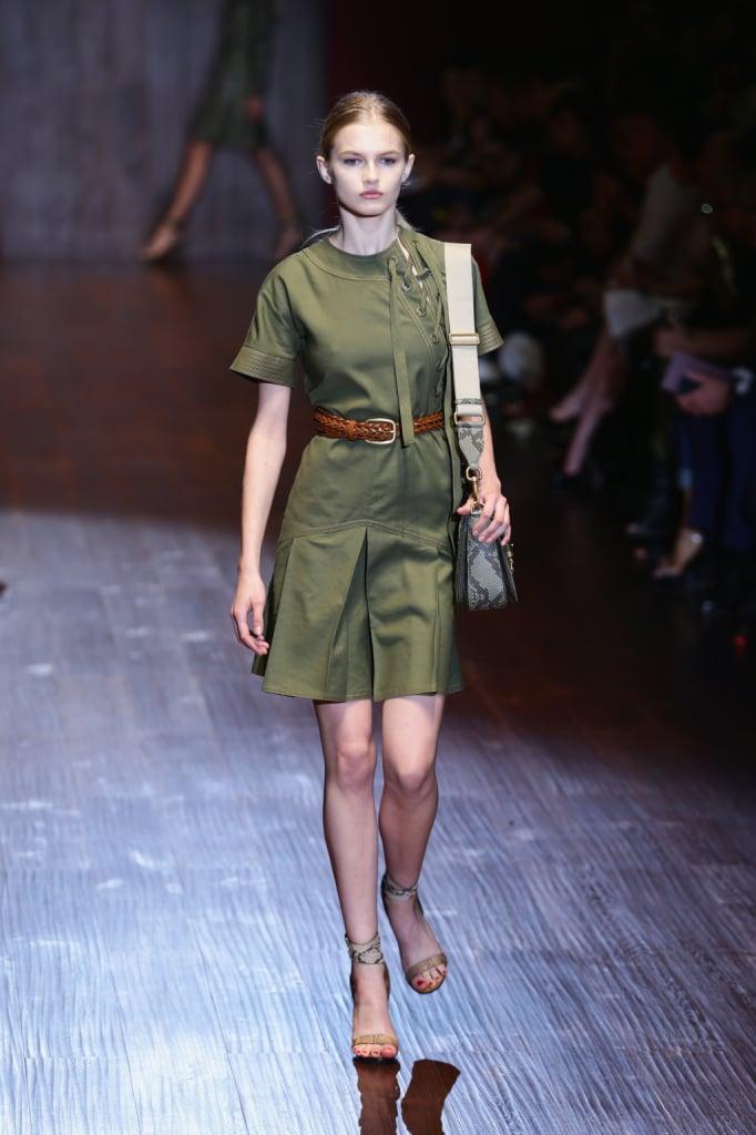 Gucci, MFW, collezione Primavera-Estate 2015: miniabito color verde militare con particolare allacciatura alla francese sulla spalla e strizzato da cintura intrecciata di cuoio in vita