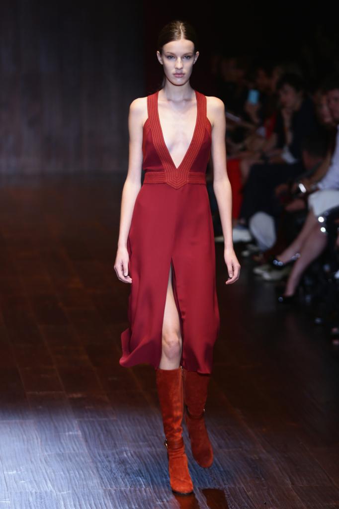 Gucci, MFW, collezione Primavera-Estate 2015: abito lungo in seta rosso marsala, avvolgente, con ampio scollo a V sul davanti e ampio spacco. Gli stivali in camoscio sono color rosso ruggine