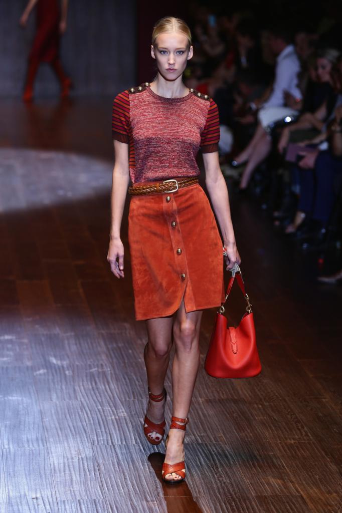 Gucci, MFW, collezione Primavera-Estate 2015: gonna al ginocchio in camoscio ruggine con motivo bottoncini dorati sul davanti ripresi anche sulle spalle della maglietta a righe nei toni del rosso