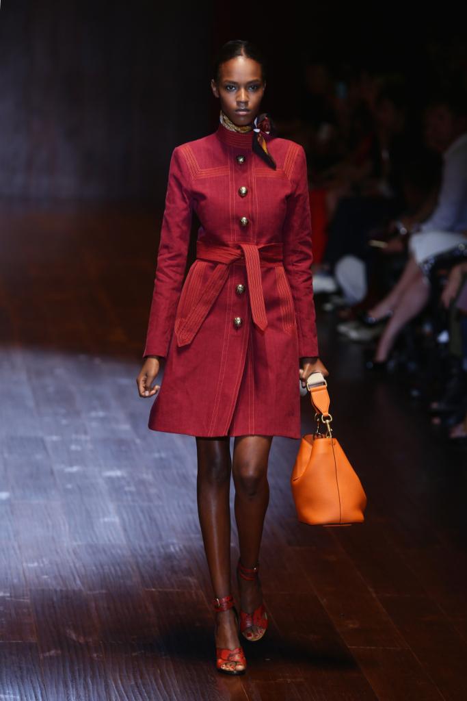 Gucci, MFW, collezione Primavera-Estate 2015: trench rosso marsala in stile militare con motivo bottoncini dorati, abbinato a borsa arancio con tracollina e sandali in pitone