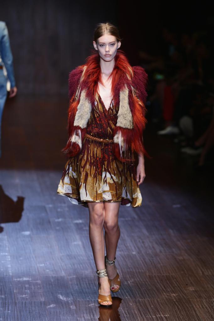 Gucci, MFW, collezione Primavera-Estate 2015: miniabito con gonna a ruota e chiusura a intreccio sul davanti, coprispalle con pelliccia e piume sui toni del rosso e arancio