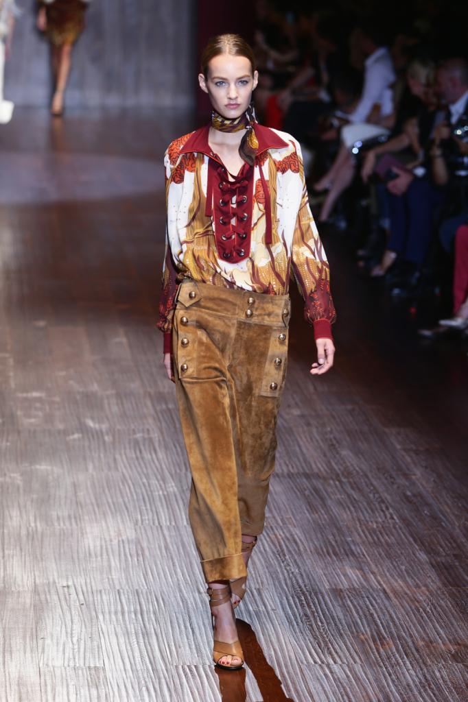Gucci, MFW, collezione Primavera-Estate 2015: pantaloni in camoscio marroni con bottoncini dorati in stile marinaresco e blusa fantasia con allacciatura alla francese
