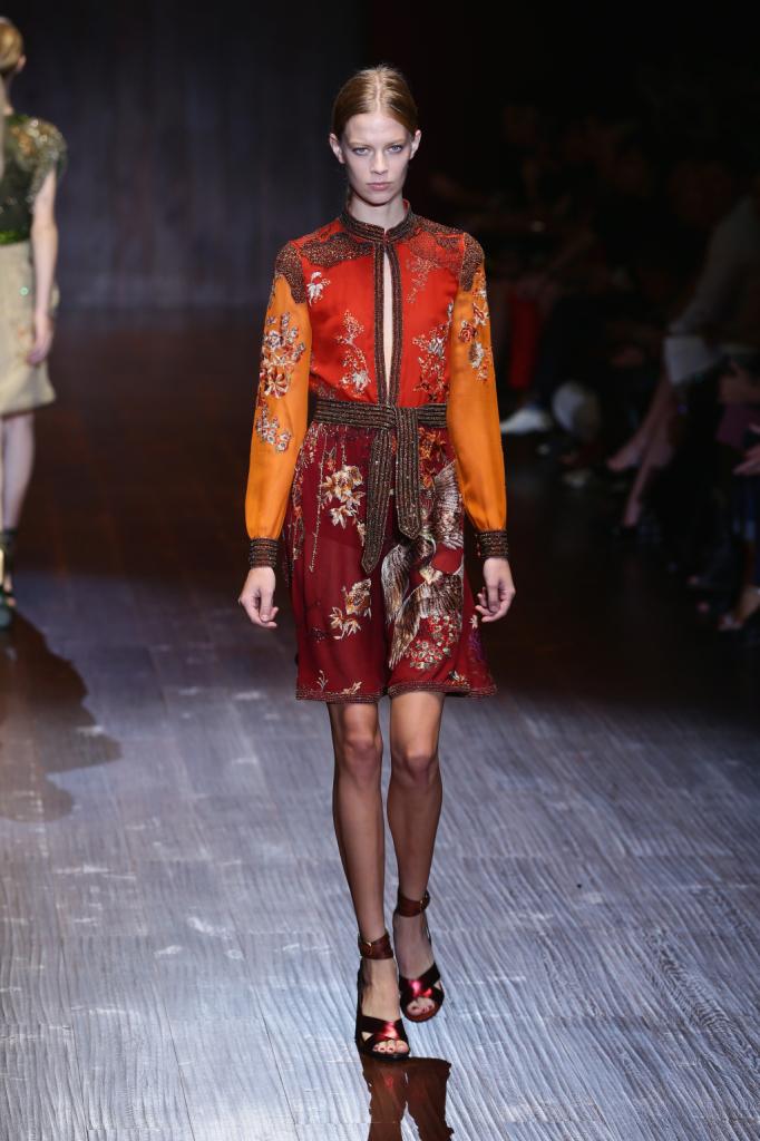 Gucci, MFW, collezione Primavera-Estate 2015: il miniabito è in leggera seta con bordi e adorni di cristalli, la fantasia ricorda l'oriente e il taglio dell'abito quello del kimono