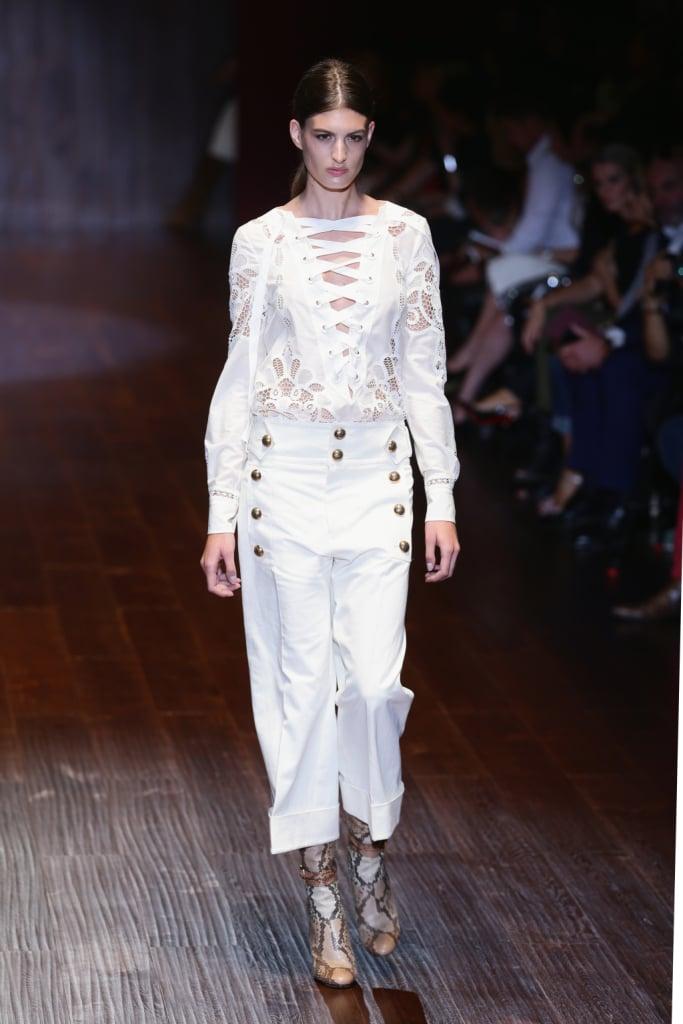 Gucci, MFW, collezione Primavera-Estate 2015: pantalone bianco in stile militare con bottoncini dorati e blusa bianca con pizzo macramè e allacciatura francese anteriore