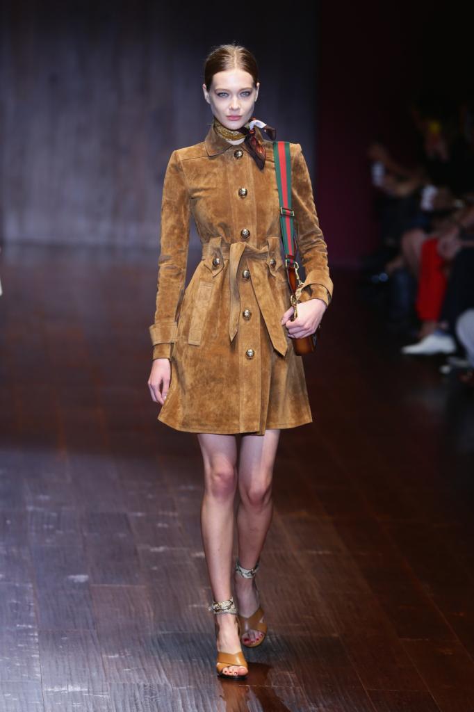Gucci, MFW, collezione Primavera-Estate 2015: trench marrone in camoscio con bottoncini dorati in stile militare, strizzato in vita da cintura e foulard fantasia al collo. Jackie bag.