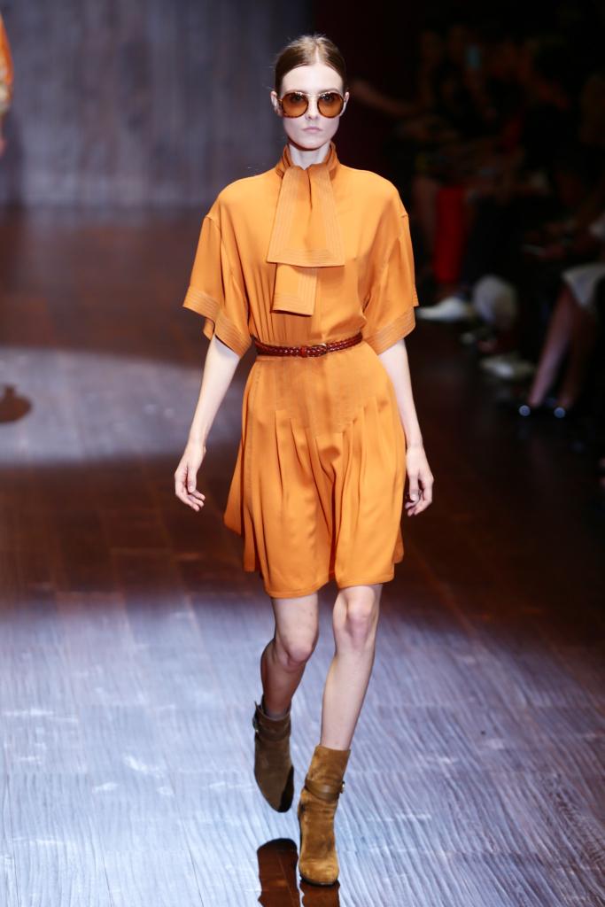 Gucci, MFW, collezione Primavera-Estate 2015: vestito in seta color arancio tangerine con collo a foulard e cintura in vita. Occhiali tondi anni Settanta con lenti tone sur tone