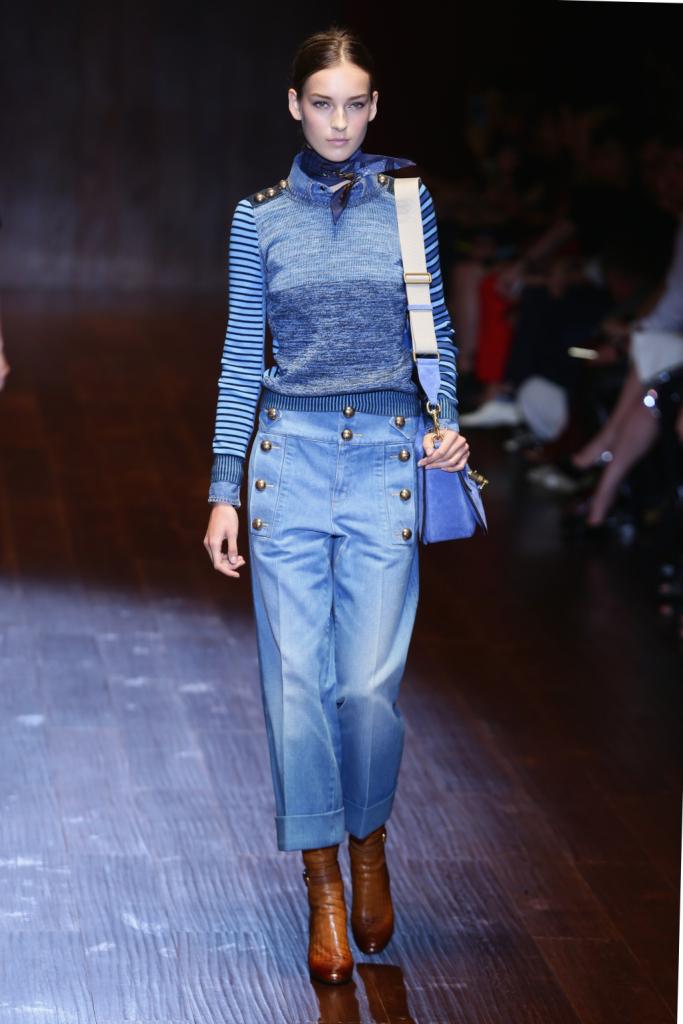Gucci, MFW, collezione Primavera-Estate 2015: denim in stile militare con bottoni dorati il cui motivo è ripreso anche sulle spalle della maglia a righe azzurre