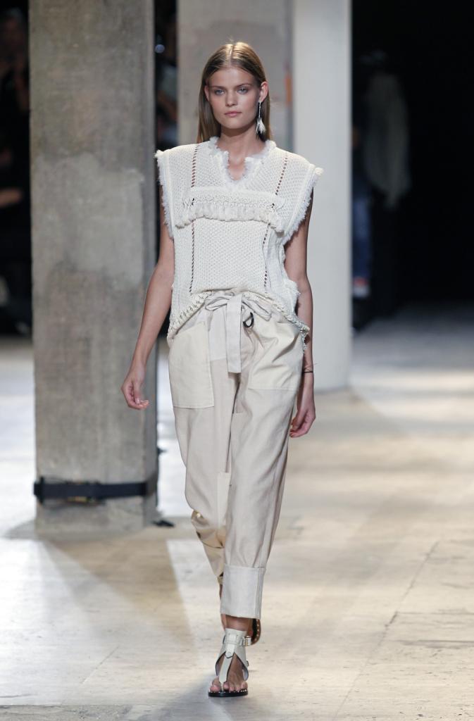 Isabel Marant, PFW, collezione Primavera-Estate 2015: pantaloni dal taglio leggermente morbido, bianchi optical con coulisse in vita e blusa traforata e decorata con nappine