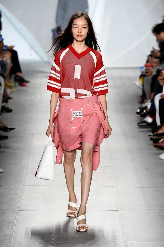 Maglia sportiva rossa con dettagli bianchi, abbinata a shorts sportivi