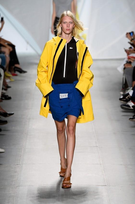 Parka oversize giallo, abbinato ad una maglia nera e shorts blu