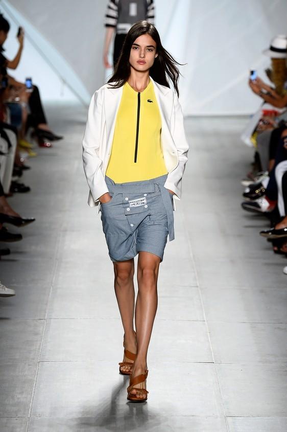 Blusa giallo fluo, abbinata ad una giacca bianca e shorts, nella tonalità grigio chiaro