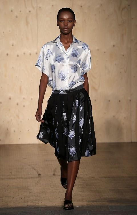 Blusa bianca con fiori azzurri e gonna a pieghe ampia, nera con fiori
