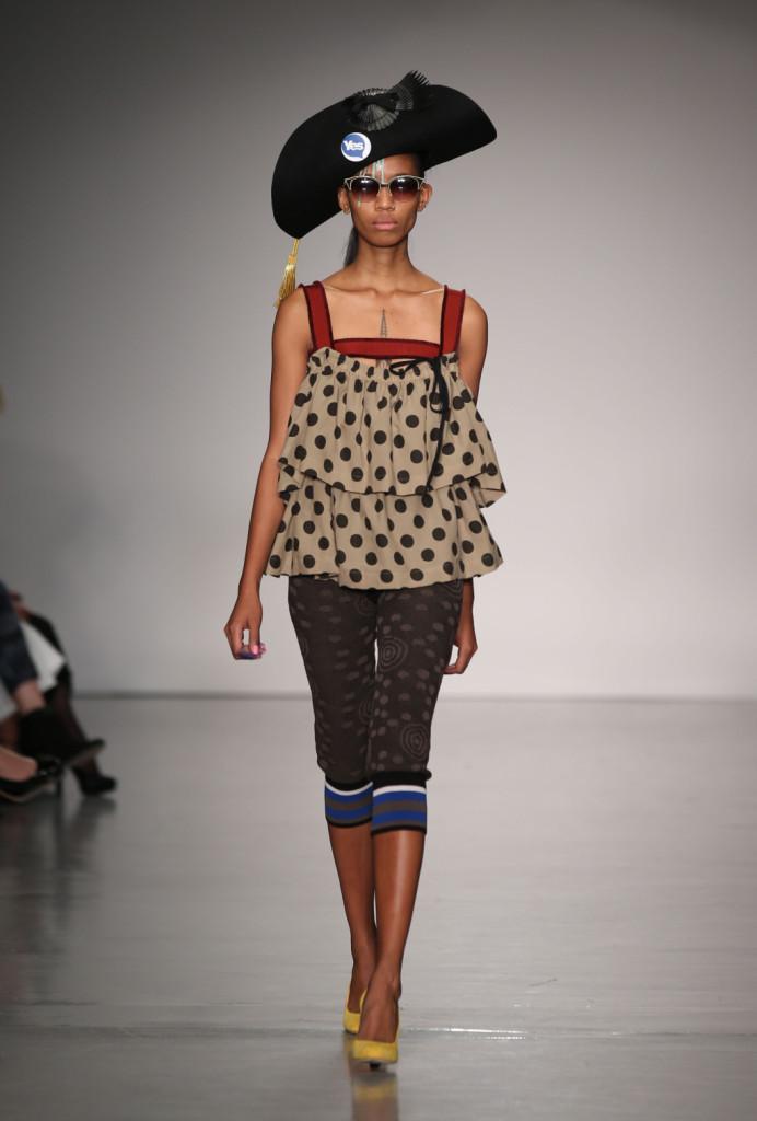 Vivienne Westwood Red Label, LFW, Primavera-estate 2015: la canotta a pois con volant sembra come appesa su passanti per tenda, i leggins sono stampati con elastico in fondo. Il cappello è da bucaniere.