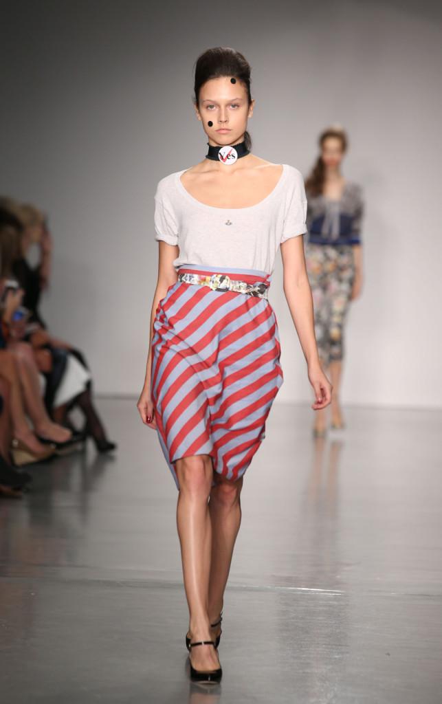 Vivienne Westwood Red Label, LFW, Primavera-estate 2015: completo con longuette- palloncino a righe e top grigio, la cintura è a fiori e sul collarino è appuntata la spilla con la scritta YES