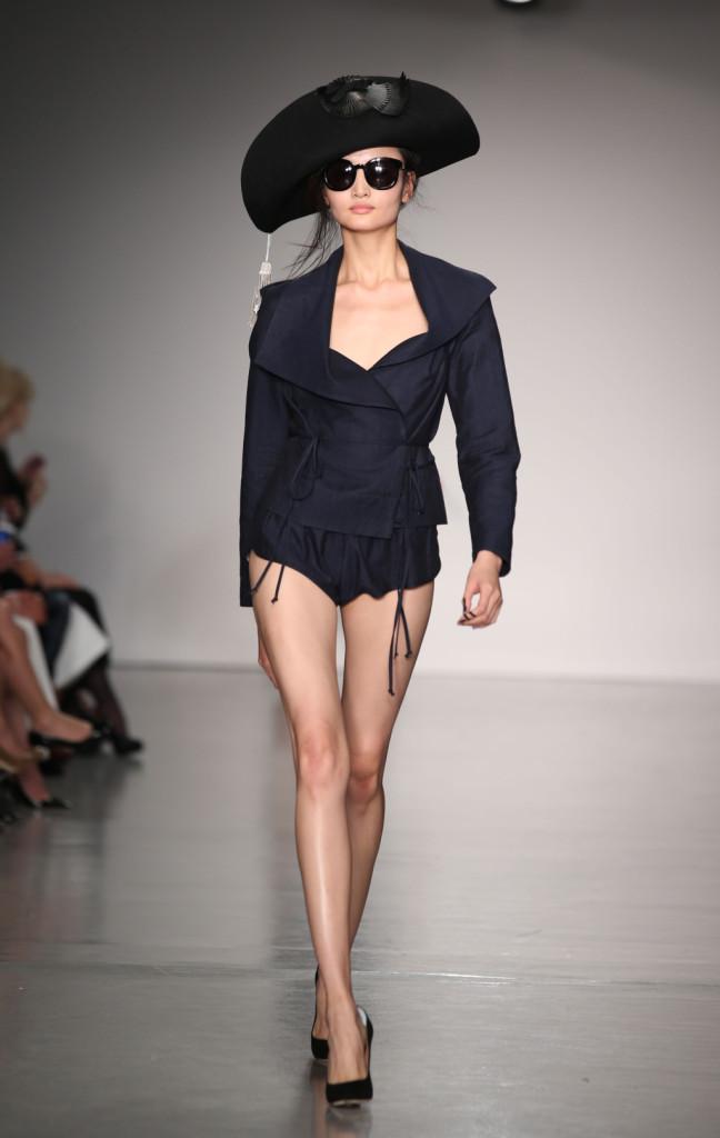 Vivienne Westwood Red Label, LFW, Primavera-estate 2015: giacca con lacci e spalline voluminose, culotte blu notte. In testa il guizzo dell'artista per la PE 2015: il cappello da corsaro