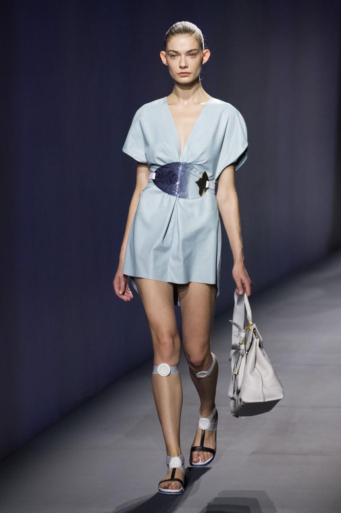 Vionnet, MFW, collezione Primavera-Estate 2015: abito corto celeste con ampio scollo a V e placca metallica trasparente. Sandali con laccio elastico appena sotto il ginocchio