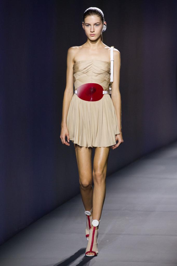 Vionnet, MFW, collezione Primavera-Estate 2015: abito corto con top a fascia drappeggiato, in chiffon color beige, fibbia metallica rosso smalto strizzata in vita
