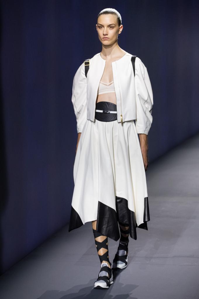 Vionnet, MFW, collezione Primavera-Estate 2015: gonna bianca con bordi asimmetrici e in pelle nera, giacchino bianco con maniche leggermente a palloncino