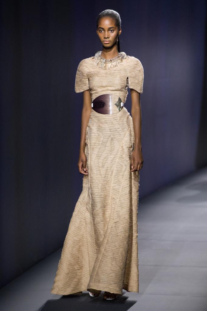 Vionnet, MFW, collezione Primavera-Estate 2015: abito lungo beige con lavorazione, la gonna si apre sul fondo e in vita è strizzata una fibbia ovale trasparente