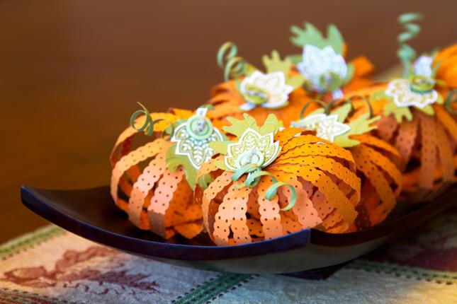 Con del nastro arancione per pacchi realizzate delle zucche di Halloween per decorare la tavola o lo studio