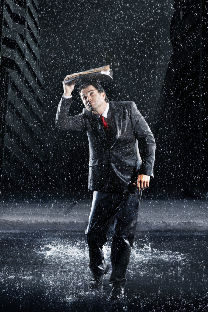 Businessman Covering Head With Binder In Rain