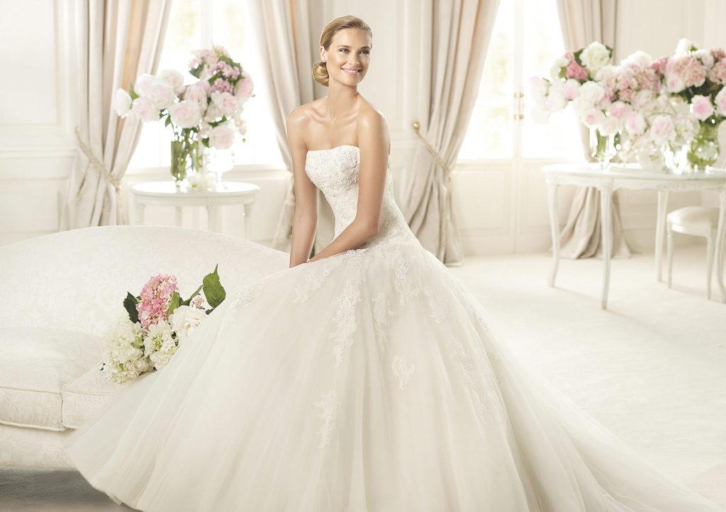 Il modello Barroco è il tipico abito dei sogni, grazie al bustino senza spalline e ai delicati motivi floreali ricamati in pizzo chantilly e alle pietre bianche che scendono dal bustino in tulle fino alla gonna ampia