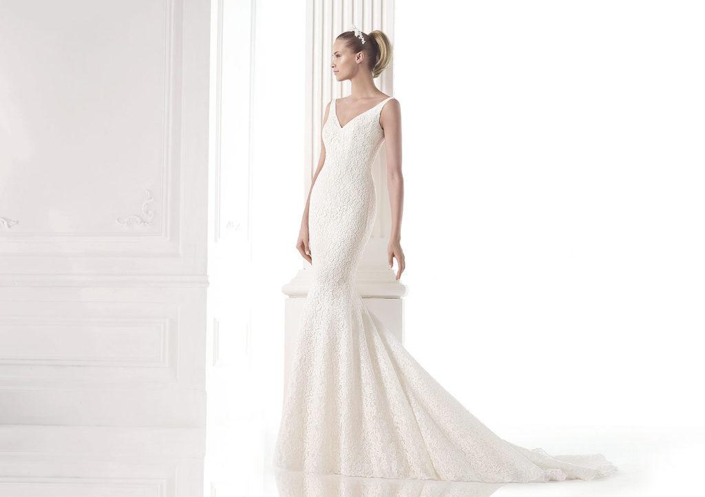 Delicato abito da sposa con corpetto in pizzo, gonna e strascico stile sirena. Corpetto con scollo a punta e profonda scollatura sulla schiena