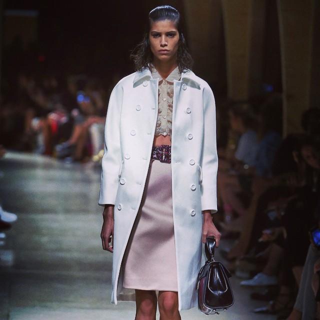 Miu Miu, PFW, collezione Primavera-Estate 2015: cappottino bianco doppiopetto stile anni Sessanta, longuette rosa confetto e camicetta tagliata con volant sul davanti