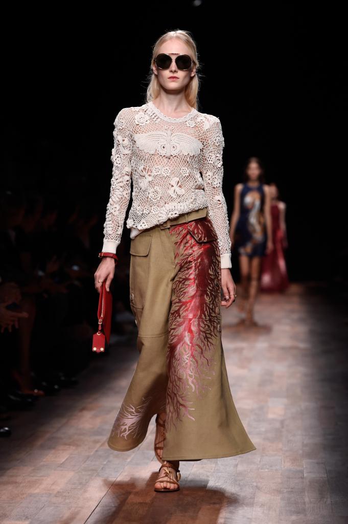 Valentino, PFW, collezione Primavera-Estate 2015: pantalone beige a palazzo con disegno corallo in rosso rubino, maglioncino bianco lavorato