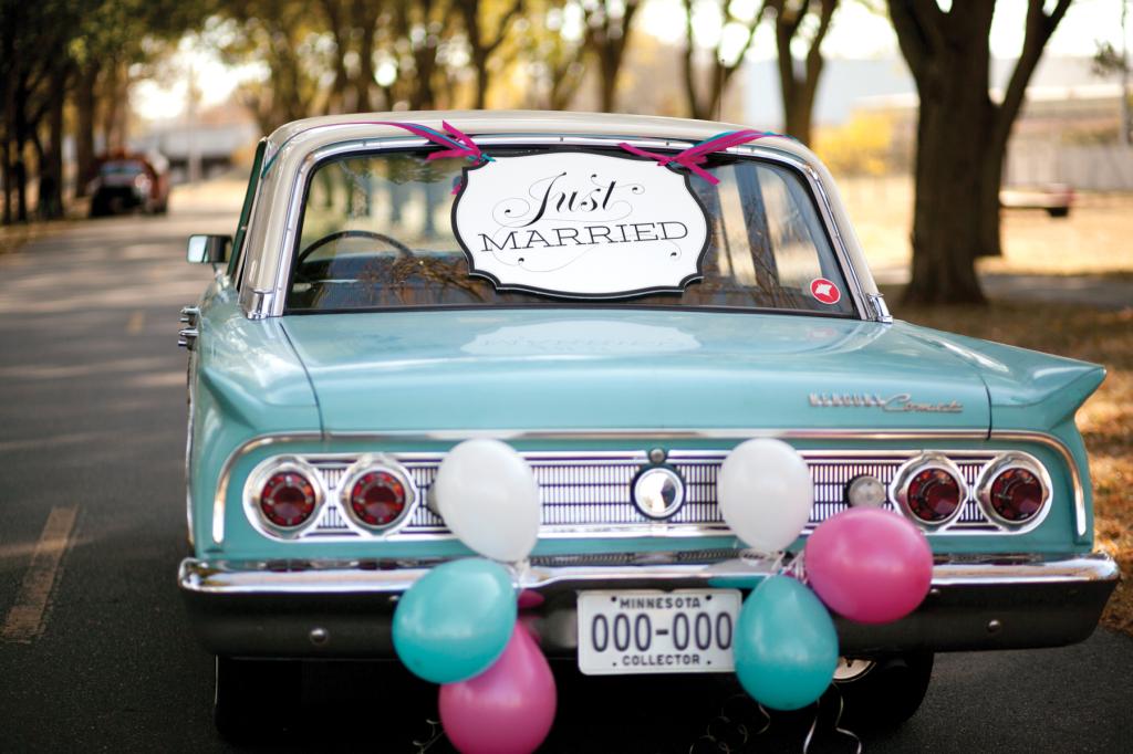 Just married su un'auto d'epoca con palloncini colorati legati alla targa auto