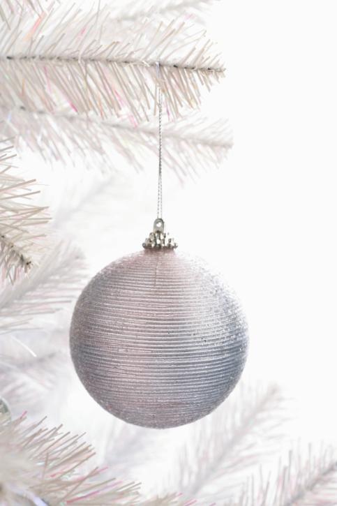 Avete optato per un albero bianco? Decoratelo con palline argentate e e fiocchetti della stessa tonalità