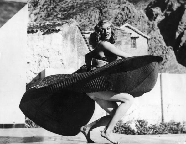 Un' Anita Ekberg giocosa balla a piedi scalzi in Spagna