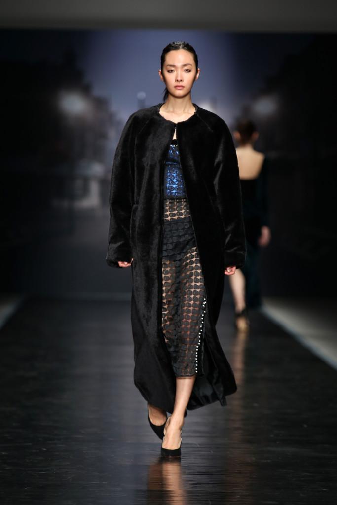 Il lungo cappotto nero copre l'abito traforato portato con l'underwear