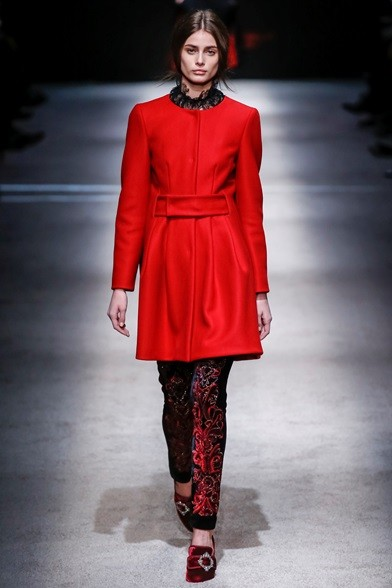Cappottino rosso stretto in vita su pantaloni di velluto damascato
