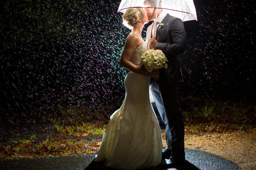 bacio romantico sposi sotto la pioggia