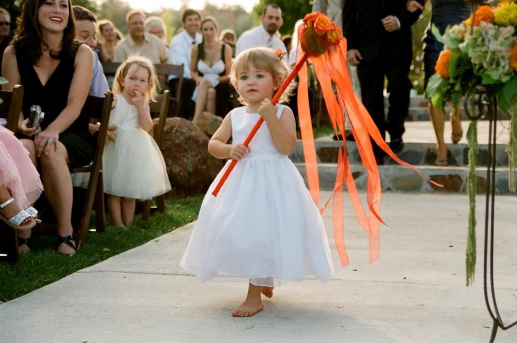piccola damigella scalza per un matrimonio campestre che porta un particolare bouquet