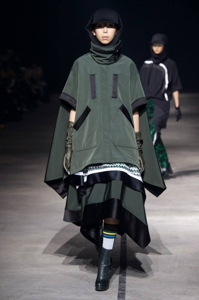 Il look loose è reso unico dalla cappa verde militare ampissima