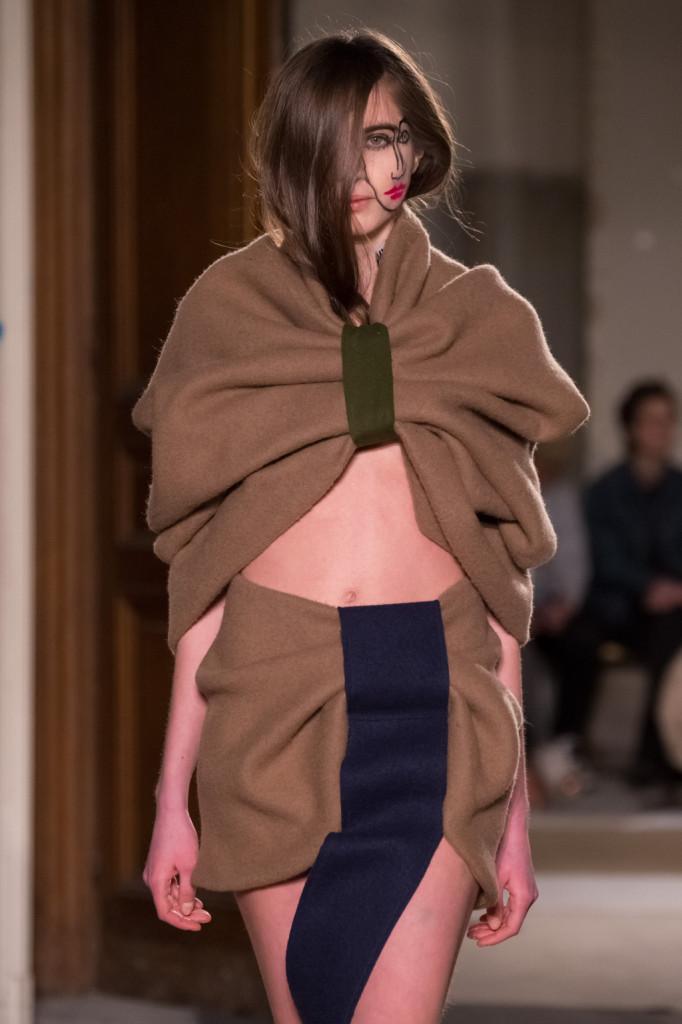 Cappa brown e giochi di drappeggi per l'outfit che svela aree strategiche
