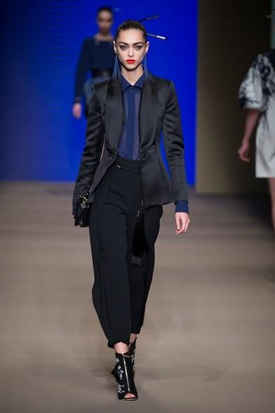 Camicia velata blu sotto il completo nero con pantaloni ampi e giacca lunga