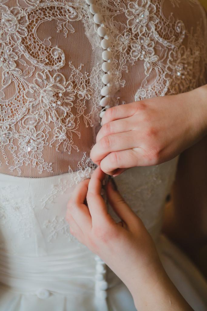la damigella aiuta la sposa a indossare l'abito nuziale