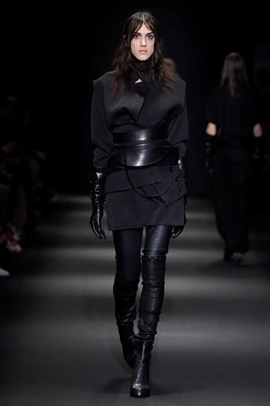 Giacca e gonna corte su leggins di pelle nera, stivali alti