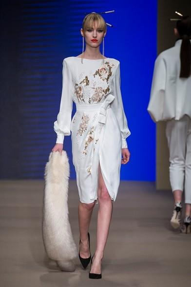 L'oro si accende sul bianco candido del vestito portato con la pelliccia