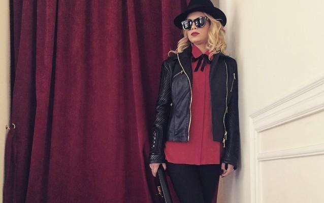 Chiodo in pelle, cappello nero e camicia rossa sono elementi costanti negli outfit di Emma