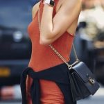Look casual per la modella con vestito e golfino legato in vita