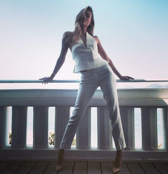 Completo total white composto da top scollato legato al collo e pantaloni leggeri a sigaretta, abbinato delle décolleté color cipria.