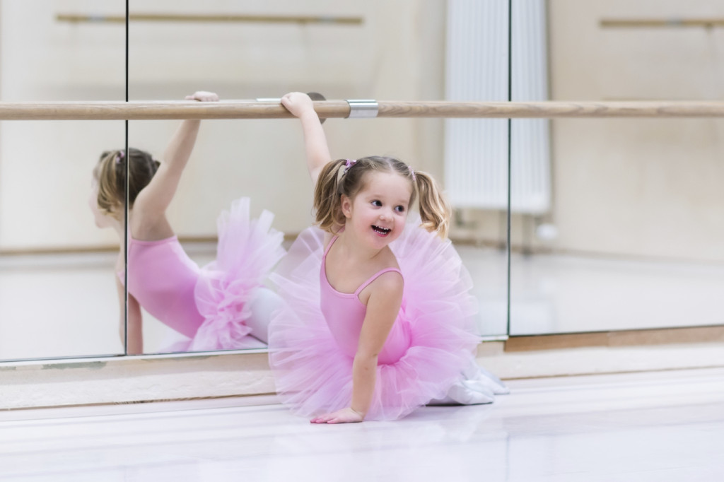Little ballerina girl in a pink tutu. Adorable child dancing classical ballet in a white studio.