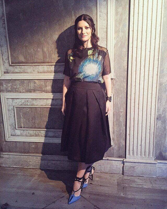 Laura Pausini con completo composto da t-shirt a maxi stampa e gonna nera.