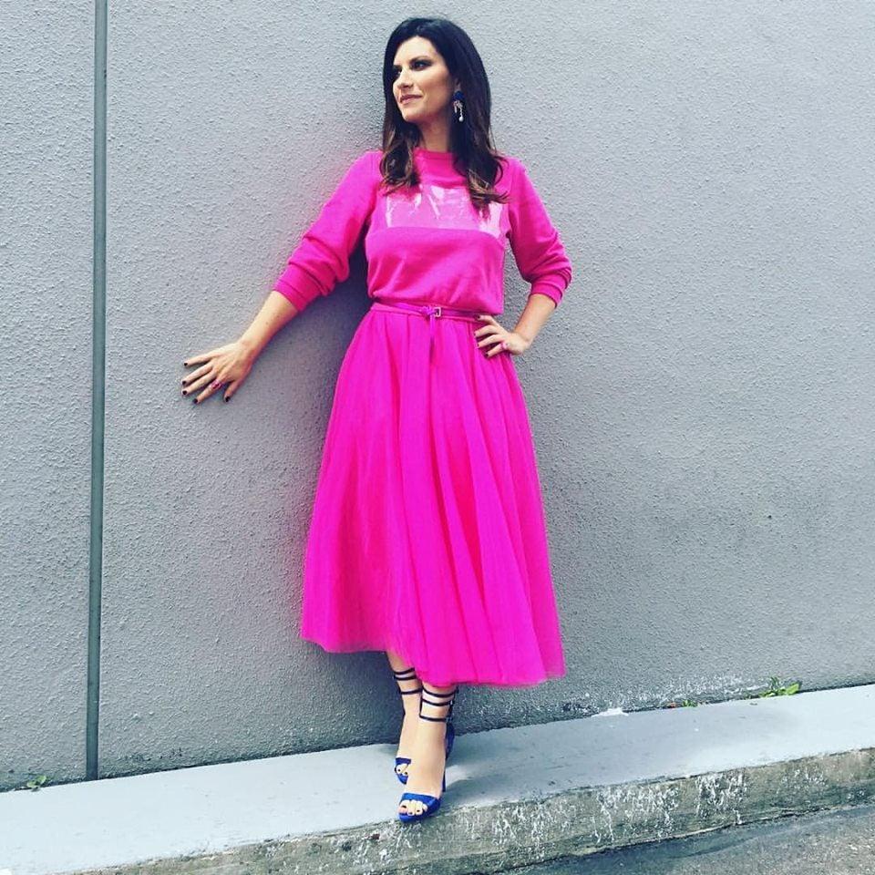 Laura Pausini con un abito fucsia e sandali blu.