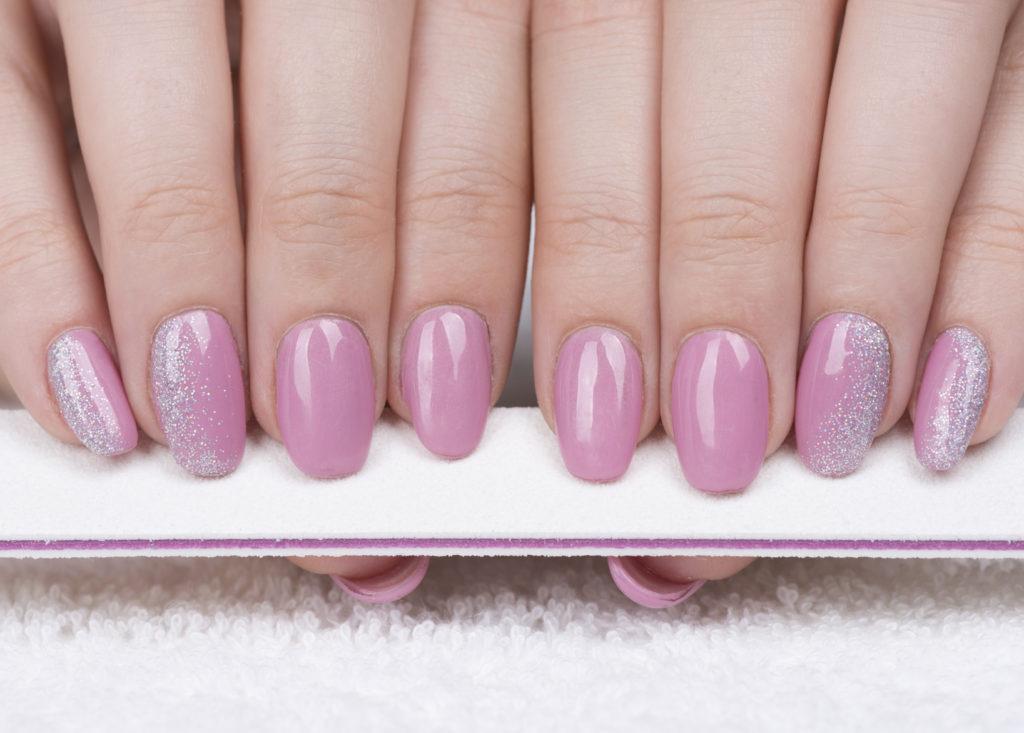 Dettagli glitter argento su unghie a mandorla rosa.